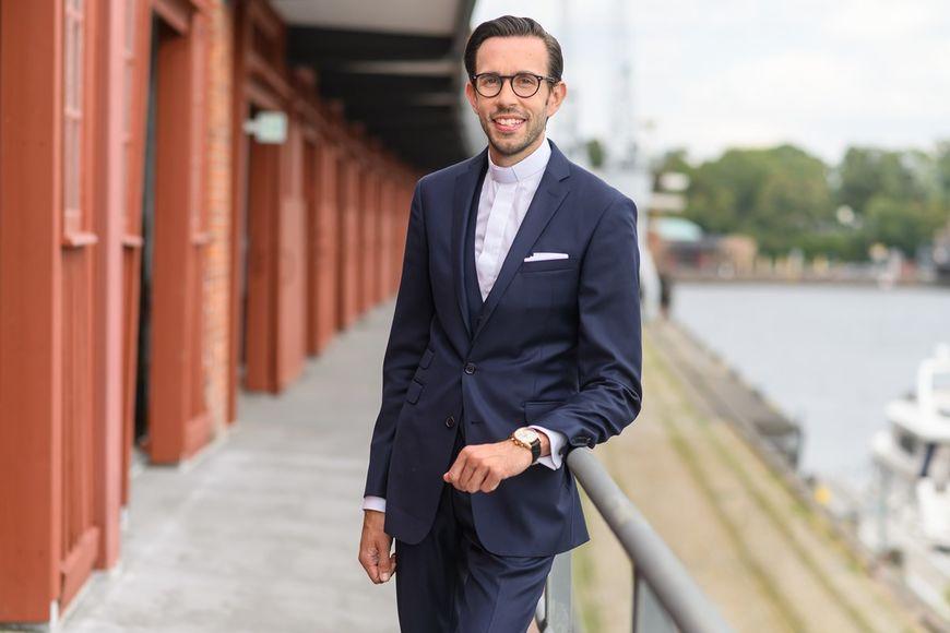 Ein Mann mit dunklem Anzug, weißem Hemd, einer Armbanduhr lehnt an einem Geländer. Er hat kurze dunkle Haare, trägt eine Brille und schaut freundlich in die Kamera. Im Hintergrund verschwommen Elemente des Lübecker Hafens. - Copyright: Guido Kollmeier